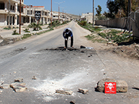 A Syrian man collects samples from the site of a suspected toxic gas attack in Khan Sheikhun in Syria. (Photo: dpa/ newscom)